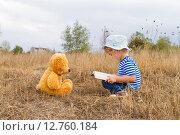 Маленькая девочка читает книгу плюшевому медведю. Стоковое фото, фотограф Вячеслав Волков / Фотобанк Лори