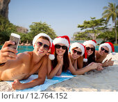 Купить «group of friends in santa hats with smartphone», фото № 12764152, снято 3 августа 2014 г. (c) Syda Productions / Фотобанк Лори
