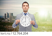 Купить «businessman in suit holding clock with 8 o'clock», фото № 12764204, снято 29 января 2015 г. (c) Syda Productions / Фотобанк Лори