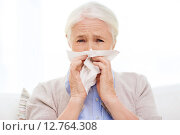 Купить «sick senior woman blowing nose to paper napkin», фото № 12764308, снято 10 июля 2015 г. (c) Syda Productions / Фотобанк Лори