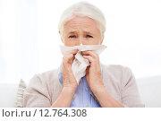 Купить «sick senior woman blowing nose to paper napkin», фото № 12764308, снято 10 июля 2015 г. (c) Syda Productions / Фотобанк Лори
