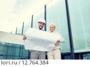 Купить «smiling businessmen with blueprint and helmets», фото № 12764384, снято 19 августа 2014 г. (c) Syda Productions / Фотобанк Лори