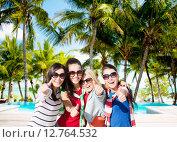 Купить «happy teenage girls showing thumbs up on beach», фото № 12764532, снято 31 августа 2013 г. (c) Syda Productions / Фотобанк Лори
