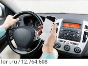 Купить «close up of man hand with smartphone driving car», фото № 12764608, снято 17 июля 2015 г. (c) Syda Productions / Фотобанк Лори