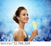 Купить «smiling woman holding glass of sparkling wine», фото № 12766324, снято 1 июня 2014 г. (c) Syda Productions / Фотобанк Лори