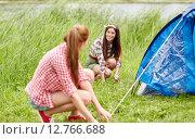 Купить «smiling friends setting up tent outdoors», фото № 12766688, снято 25 июля 2015 г. (c) Syda Productions / Фотобанк Лори