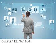 Купить «businessman with contacts icons on virtual screen», фото № 12767104, снято 29 января 2015 г. (c) Syda Productions / Фотобанк Лори