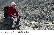 Купить «Пожилой мужчина турист с рюкзаком отдыхает на камне во время подъема на горный перевал. Хибины, Кольский полуостров», видеоролик № 12769916, снято 2 сентября 2015 г. (c) Кекяляйнен Андрей / Фотобанк Лори