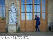 Девушка фотографирует скульптуру у входа в Большой Гатчинский дворец (2015 год). Редакционное фото, фотограф Виктор Карасев / Фотобанк Лори