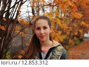 Купить «Девочка на фоне деревьев с оранжевыми листьями», фото № 12853312, снято 20 сентября 2015 г. (c) Ирина Здаронок / Фотобанк Лори