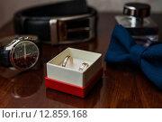 Свадебные обручальные кольца и аксессуары жениха лежат на столе. Стоковое фото, фотограф Игорь Низов / Фотобанк Лори