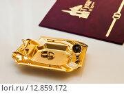 Свадебные обручальные кольца лежат на подносе на столе в ЗАГСе на фоне папки с документами. Стоковое фото, фотограф Игорь Низов / Фотобанк Лори