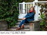 Купить «Счастливая девушка сидит на деревянном крыльце загородного дома», эксклюзивное фото № 12867864, снято 1 октября 2015 г. (c) Игорь Низов / Фотобанк Лори