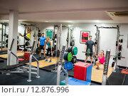 Купить «Fit people working out in weights room», фото № 12876996, снято 19 июля 2015 г. (c) Wavebreak Media / Фотобанк Лори
