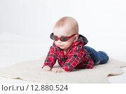 Купить «Модный малыш в темных очках лежит на коврике», фото № 12880524, снято 19 ноября 2018 г. (c) Efanov Aleksey / Фотобанк Лори