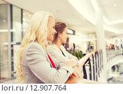 Купить «happy young women in mall or business center», фото № 12907764, снято 3 ноября 2014 г. (c) Syda Productions / Фотобанк Лори