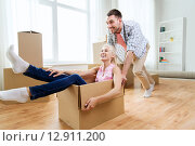 Купить «couple with cardboard boxes having fun at new home», фото № 12911200, снято 6 июня 2015 г. (c) Syda Productions / Фотобанк Лори