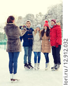 Купить «happy friends with smartphone on ice skating rink», фото № 12912032, снято 22 декабря 2014 г. (c) Syda Productions / Фотобанк Лори