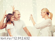 Купить «happy family with camera taking picture at home», фото № 12912632, снято 1 марта 2014 г. (c) Syda Productions / Фотобанк Лори