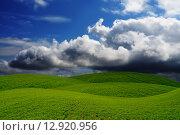 Купить «Зеленые холмы на фоне неба с облаками», фото № 12920956, снято 13 июня 2015 г. (c) Сергей Эшметов / Фотобанк Лори