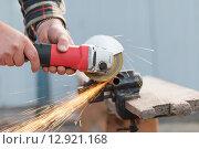 Купить «Руки режут металлическую трубу с помощью болгарки (УШМ)», фото № 12921168, снято 17 октября 2015 г. (c) Владимир Семенчук / Фотобанк Лори