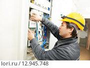 Купить «Electrician installing energy saving meter», фото № 12945748, снято 16 марта 2012 г. (c) Дмитрий Калиновский / Фотобанк Лори