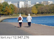 Купить «Осень в Коломенском. Две пожилые женщины прогуливаются по набережной Москва-реки с палками для скандинавской хотьбы», фото № 12947276, снято 21 октября 2015 г. (c) Natalya Sidorova / Фотобанк Лори