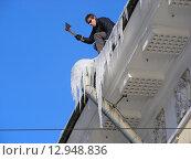 Купить «Работник сбивает топором сосульки с крыши», эксклюзивное фото № 12948836, снято 23 февраля 2010 г. (c) lana1501 / Фотобанк Лори