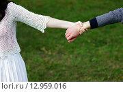 Девушка тянет за руку парня на зеленом фоне. Стоковое фото, фотограф Виктор Колдунов / Фотобанк Лори