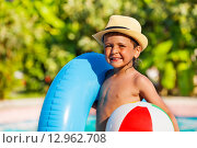 Купить «Веселый мальчик с надувным кругом и мячом возле бассейна», фото № 12962708, снято 25 июля 2015 г. (c) Сергей Новиков / Фотобанк Лори