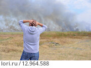 Купить «Мужчина держится за голову, глядя на горящее поле», фото № 12964588, снято 30 сентября 2015 г. (c) Станислав Самойлик / Фотобанк Лори