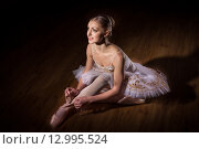 Балерина в белой пачке сидит на полу и завязывает пуанты.  Низкий ключ. Стоковое фото, фотограф Елена Троян / Фотобанк Лори