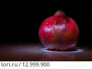Целый красный гранат на черном фоне. Стоковое фото, фотограф Юлия Добычина/Iuliia Dobychina / Фотобанк Лори