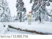 Женщина в вязаной шапке и свитере стоит с чашкой в руках в заснеженном лесу зимой. Стоковое фото, фотограф Petri Jauhiainen / Фотобанк Лори