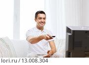 Купить «smiling man with remote control watching tv», фото № 13008304, снято 29 января 2015 г. (c) Syda Productions / Фотобанк Лори