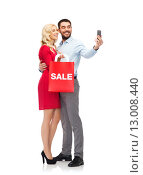 Купить «happy couple with smartphone and shopping bag», фото № 13008440, снято 3 октября 2015 г. (c) Syda Productions / Фотобанк Лори