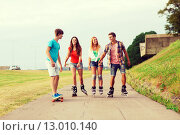 Купить «group of smiling teenagers with roller-skates», фото № 13010140, снято 10 августа 2014 г. (c) Syda Productions / Фотобанк Лори