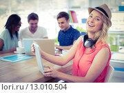 Купить «Smiling creative businesswoman working with co-workers», фото № 13010504, снято 5 июня 2015 г. (c) Wavebreak Media / Фотобанк Лори