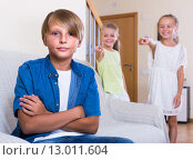 Two girls talking and sulky boy sitting separately at home. Стоковое фото, фотограф Яков Филимонов / Фотобанк Лори