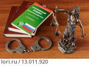 Купить «Фигурка Фемиды, наручники и Уголовный кодекс на деревянном столе», фото № 13011920, снято 29 октября 2015 г. (c) Денис Ларкин / Фотобанк Лори