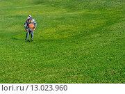 Уход за газонами. Садовник подстригает траву триммером. Редакционное фото, фотограф Игорь Яковлев / Фотобанк Лори