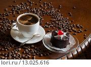 Чёрный кофе и пирожное на деревянной столешнице с кофейными зёрнами. Стоковое фото, фотограф Ольга Данилова / Фотобанк Лори