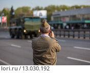 Купить «Мужчина в пилотке снимает на смартфон военную технику, которая возвращается с парада Победы. 9 мая 2015 года», фото № 13030192, снято 9 мая 2015 г. (c) megastocker / Фотобанк Лори