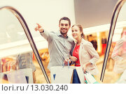 Купить «happy young couple with shopping bags in mall», фото № 13030240, снято 10 ноября 2014 г. (c) Syda Productions / Фотобанк Лори
