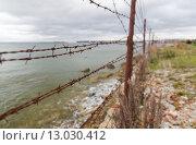 Купить «barb wire fence over gray sky and sea», фото № 13030412, снято 30 сентября 2015 г. (c) Syda Productions / Фотобанк Лори