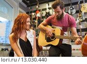 Купить «couple of musicians with guitar at music store», фото № 13030440, снято 11 декабря 2014 г. (c) Syda Productions / Фотобанк Лори