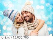 Купить «happy couple in winter clothes hugging over lights», фото № 13030700, снято 3 октября 2015 г. (c) Syda Productions / Фотобанк Лори