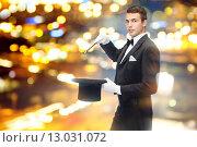 Купить «magician in top hat with magic wand showing trick», фото № 13031072, снято 12 сентября 2013 г. (c) Syda Productions / Фотобанк Лори