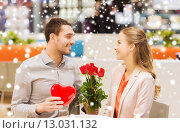 Купить «happy couple with present and flowers in mall», фото № 13031132, снято 10 ноября 2014 г. (c) Syda Productions / Фотобанк Лори