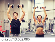 Купить «smiling man and woman with dumbbells in gym», фото № 13032080, снято 30 ноября 2014 г. (c) Syda Productions / Фотобанк Лори